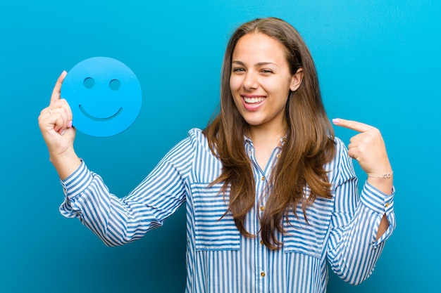 Young woman with a smiley face against blue background