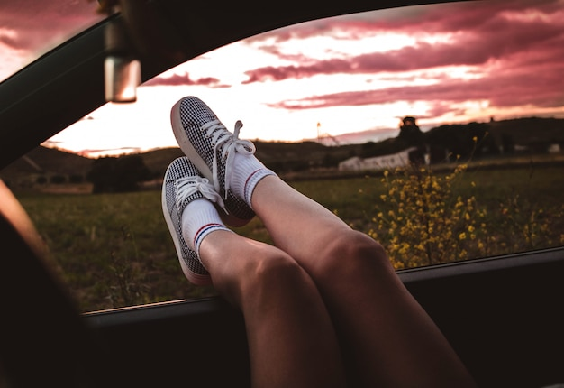 Young woman with sneakers with feet propped on the car window at sunset