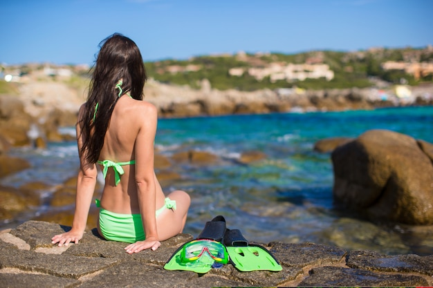 Young woman with snorkeling equipment on big stones