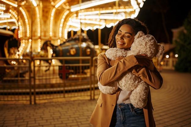 Молодая женщина с мягкой игрушкой возле карусели в ночном парке развлечений. влюбленная пара расслабиться на открытом воздухе, кольцевой аттракцион с огнями. семейный отдых летом, развлекательная тематика
