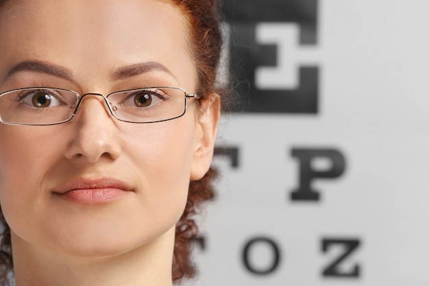 Молодая женщина в очках на диаграмме проверки зрения