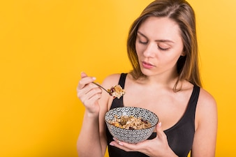 Young woman with spoon and bowl of flakes