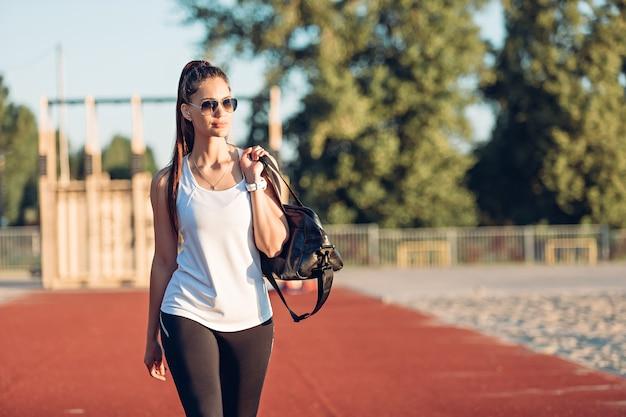 스포츠 가방을 들고 운동장을 걷는 젊은 여성