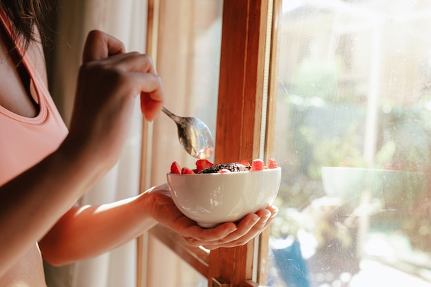 Young woman with sports bra eating breakfast bowl of fruit yogurt seeds and chocolate