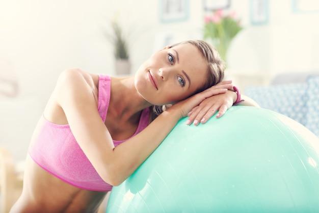Молодая женщина со спортивным инвентарем дома.