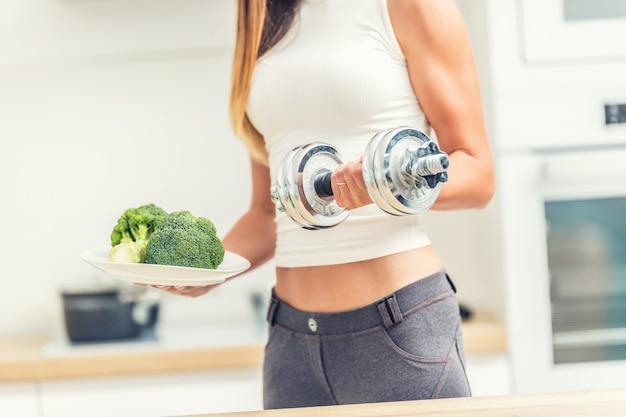 Молодая женщина со спортивной фигурой на кухне, держа в руках гантели и тарелку брокколи.