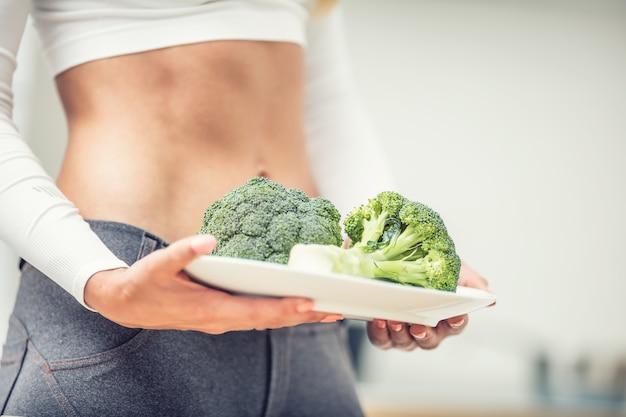 Молодая женщина со спортивной фигурой на кухне, держа в руках тарелку брокколи.