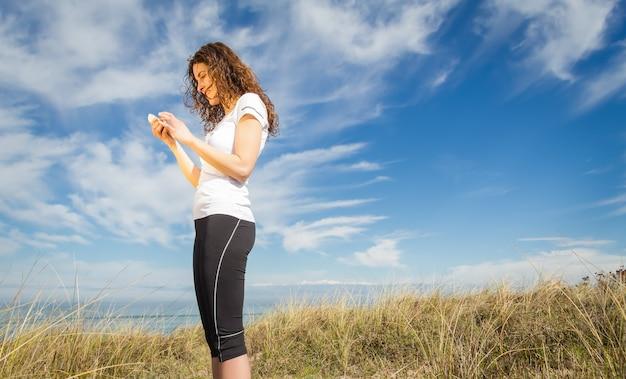 스마트폰을 보고 있는 운동복을 입은 젊은 여성