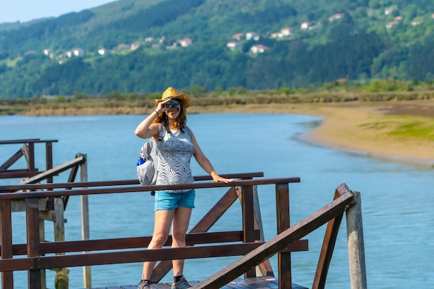 A young woman with spyglasses looking at the birds from the wooden piers of the urdaibai marshes, a biosphere reserve in bizkaia next to mundaka. basque country