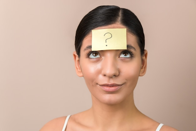 Young woman with a sticker on her forehead with a question mark on it