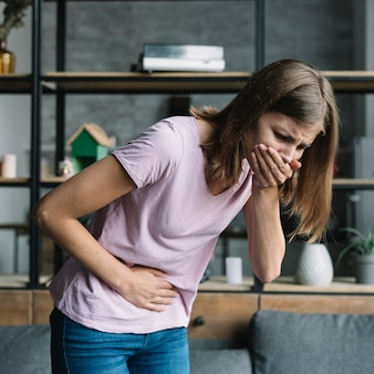 Young woman with stomach pain suffering from nausea