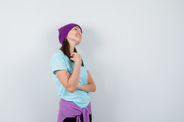 Young woman with strands of hair, looking upward in blue t-shirt, purple beanie and looking cheery , front view.