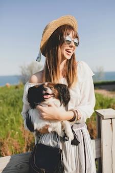Giovane donna con cappello di paglia con il suo cane dal recinto in campagna