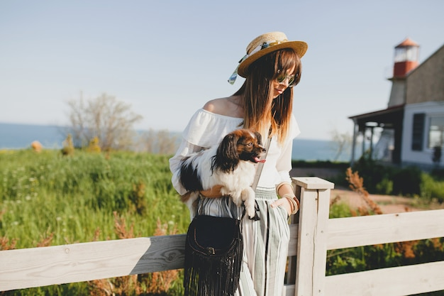 시골에서 울타리에 의해 그녀의 강아지와 함께 밀짚 모자와 젊은 여자