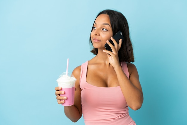 Young woman with strawberry milkshake isolated on blue background keeping a conversation with the mobile phone with someone