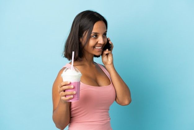 Young woman with strawberry milkshake isolated on blue background keeping a conversation with the mobile phone