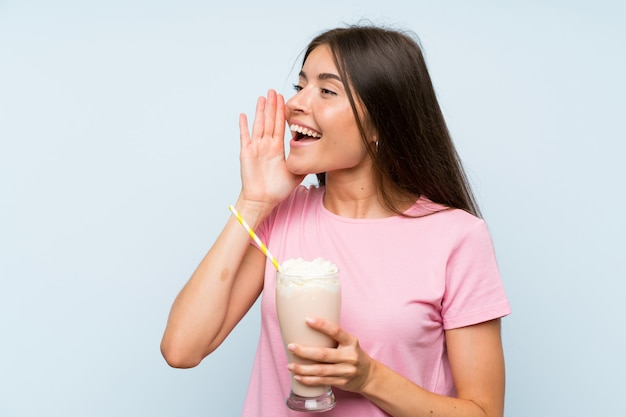 Young woman with strawberry milkshake over isolated blue background shouting with mouth wide open