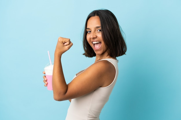 Young woman with strawberry milkshake isolated on blue celebrating a victory