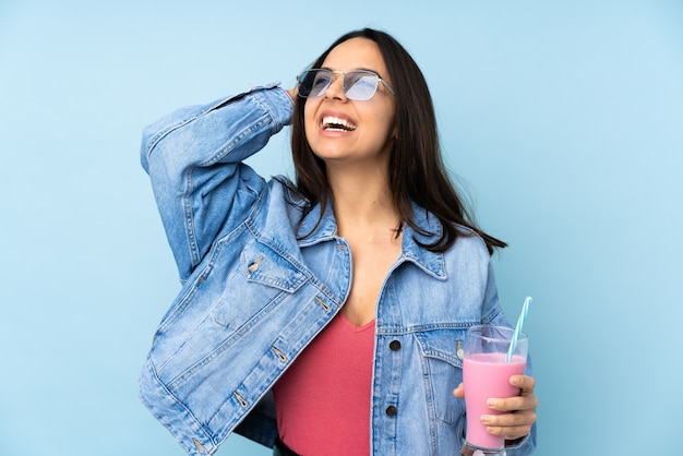 Young woman with strawberry milkshake on isolated blue smiling a lot
