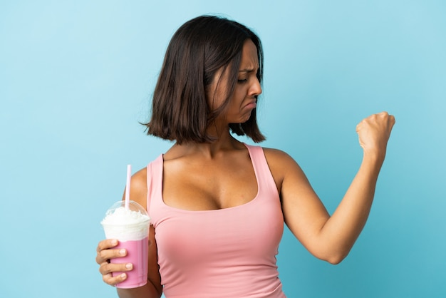 Young woman with strawberry milkshake isolated on blue wall doing strong gesture