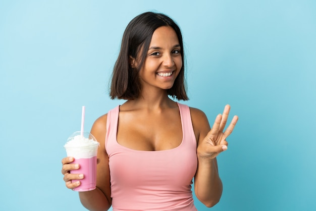 Young woman with strawberry milkshake isolated on blue wall happy and counting three with fingers