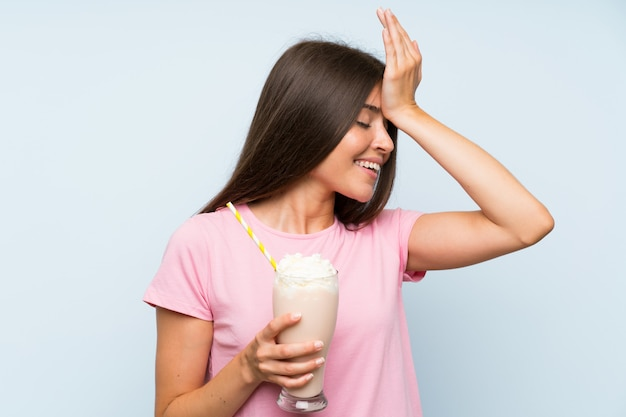 Young woman with strawberry milkshake over isolated blue wall has realized something and intending the solution
