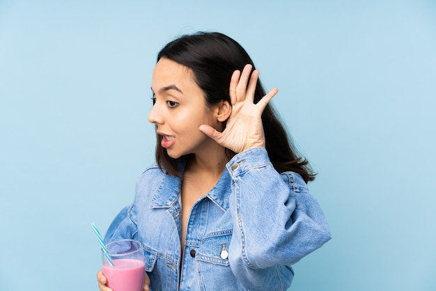 Young woman with strawberry milkshake over isolated blue wall listening to something by putting hand on the ear
