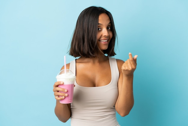 Young woman with strawberry milkshake isolated on blue wall making money gesture