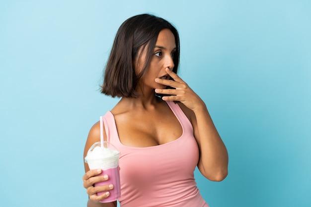 側を見ながら驚きのジェスチャーをしている青い背景に分離されたイチゴのミルクセーキと若い女性