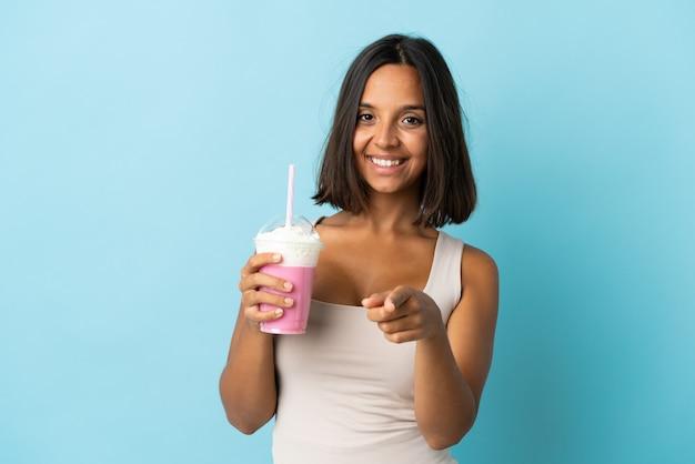 幸せな表情で正面を指す青い背景に分離されたイチゴミルクセーキと若い女性