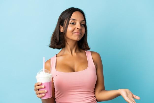 의심을 갖는 파란색 벽에 고립 된 딸기 밀크 쉐이크와 젊은 여자