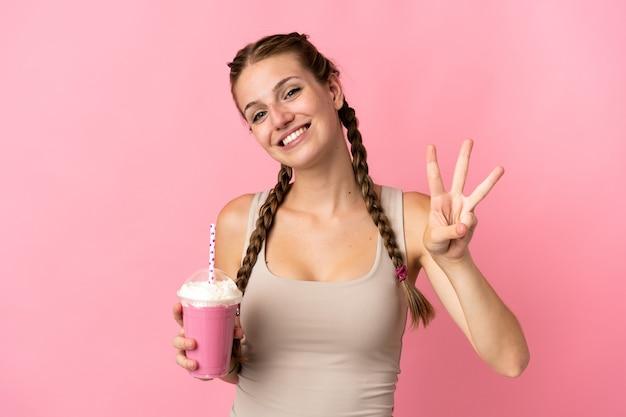 幸せなピンクの背景に分離されたイチゴのミルクセーキと指で3を数える若い女性