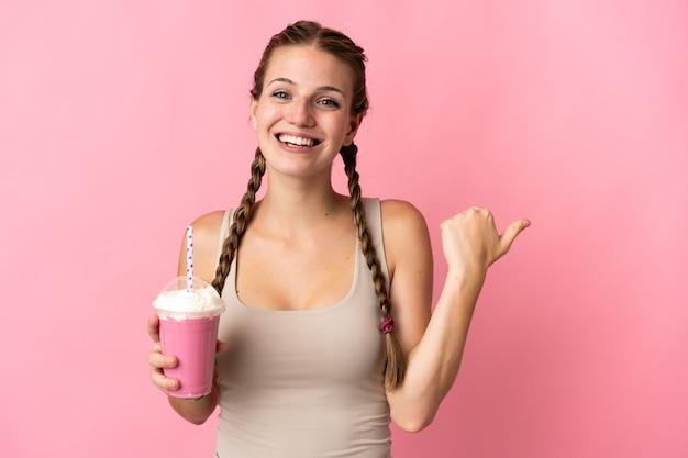 製品を提示する側を指しているピンクの背景に分離されたイチゴのミルクセーキを持つ若い女性