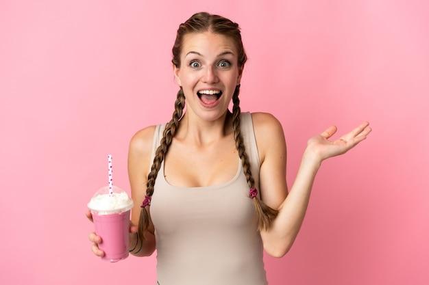 ショックを受けた表情でピンクの背景に分離されたイチゴミルクセーキと若い女性