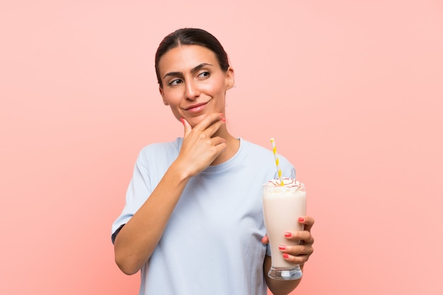 Young woman with strawberry milkshake over isolated pink wall thinking an idea