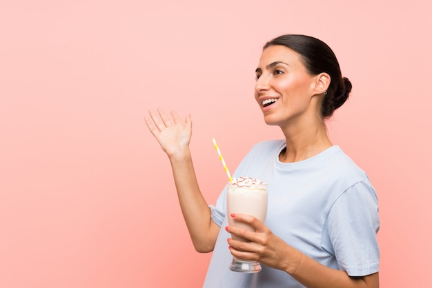 Young woman with strawberry milkshake over isolated pink wall with surprise facial expression