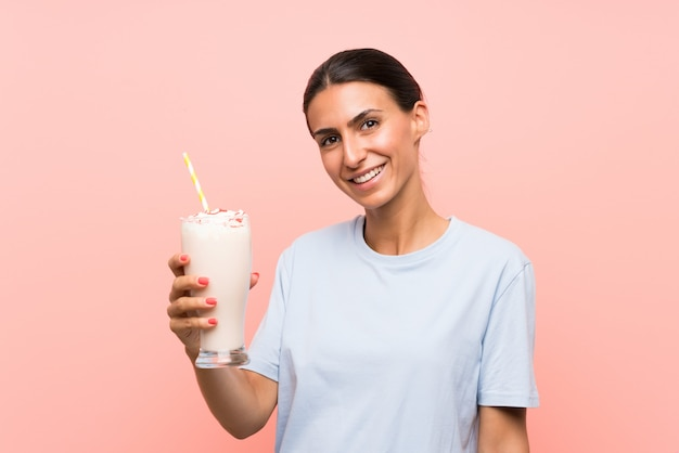 Young woman with strawberry milkshake over isolated pink wall