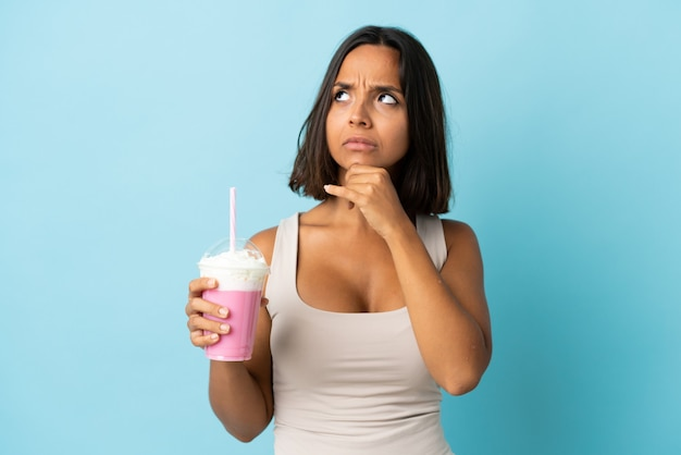 Young woman with strawberry milkshake isolated
