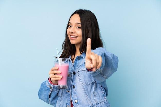 孤立した青い指を示して持ち上げてイチゴミルクセーキと若い女性