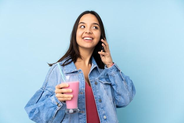 持ち帰り用のコーヒーと携帯電話を保持している孤立した青い壁にイチゴのミルクセーキを持つ若い女性