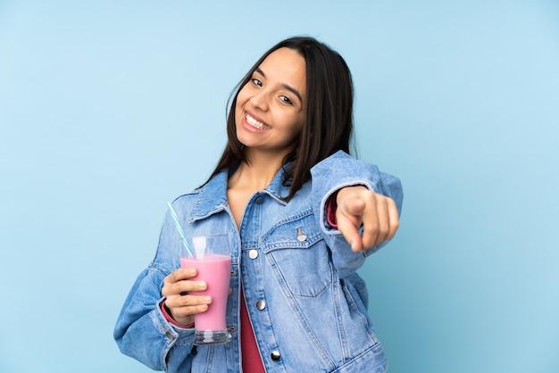 電話のジェスチャーをし、正面を指して孤立した青い壁にイチゴのミルクセーキと若い女性