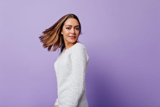 Giovane donna con orecchini a bottone e capelli scuri lisci si trasforma efficacemente con pareti viola