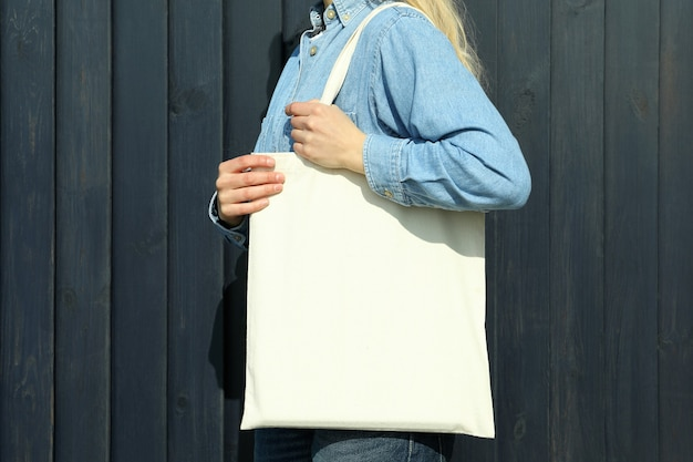 Young woman with stylish eco bag on wooden background