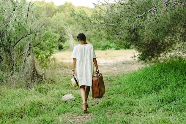 単独で悲しいまま歩いている森のスーツケースと麦わら帽子を持つ若い女性。