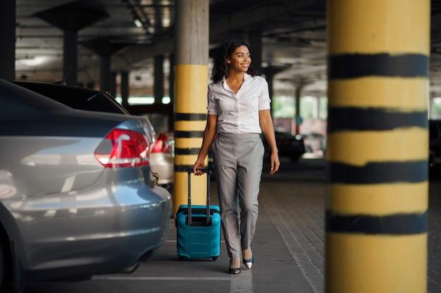 駐車場でスーツケースを持つ若い女性。駐車場に荷物を持った女性旅行者、バッグを持った乗客。手荷物を持つ少女