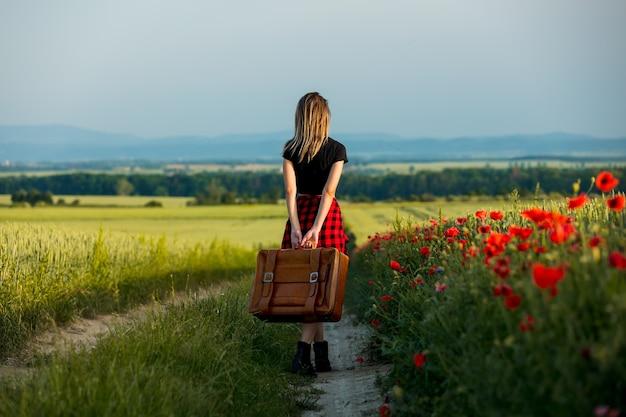 여름 시간에 시골 길에 가방을 든 젊은 여자