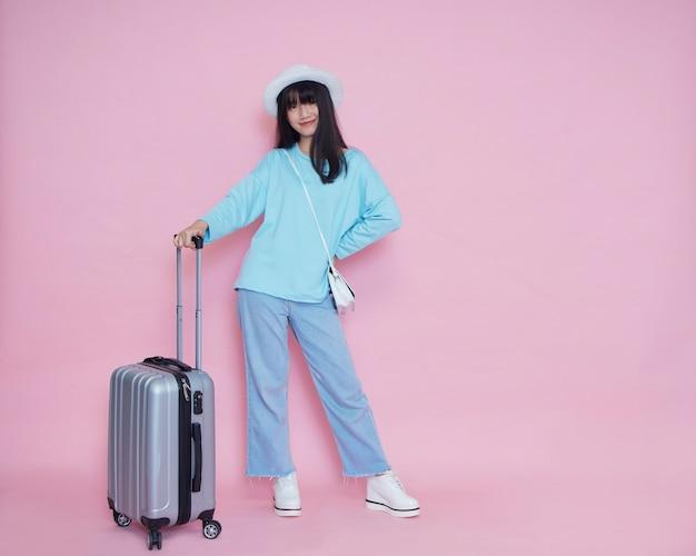 ピンクの壁にスーツケースを持つ若い女性