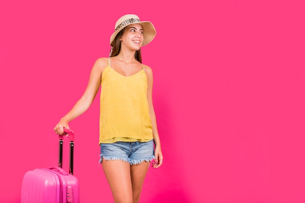 Young woman with suitcase on pink background