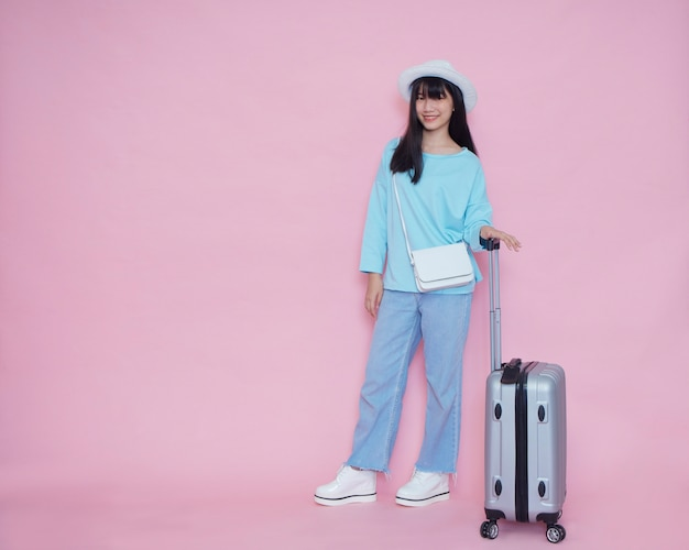 Young woman with suitcase on pink wall