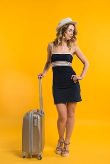 Young woman with suitcase waiting for flight